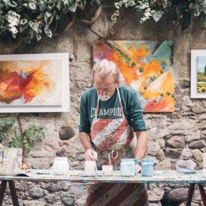 Older man mixing paints in his studio
