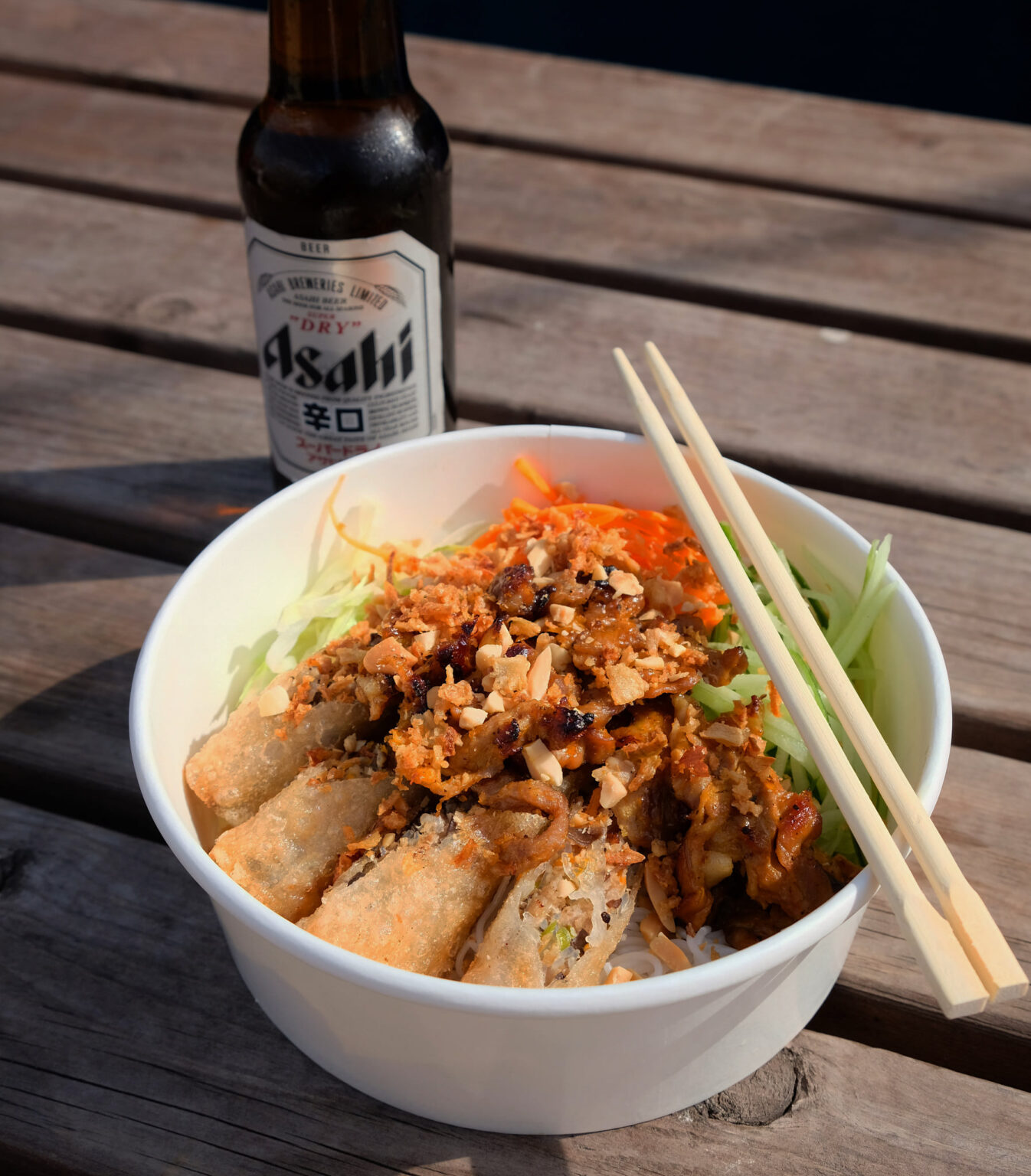 Bowl of Vietnamese food with chopsticks and bottle of beer.