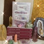 """""""The Crystal Code"""" book by Tamara Driessen on display in Crystal Eclipse at Beach Street Felixstowe surrounded by various crystals and gems"""